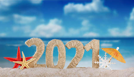 Concept of celebrating the new year in hot countries. The inscription 2021 in the sand and a snowflake under the snow on a bright day on the beach