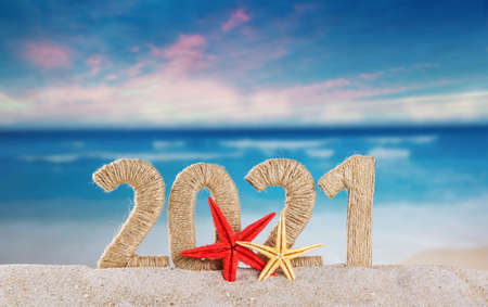 New year lettering 2021 decorated with starfish in the sand on a sunny beach Standard-Bild