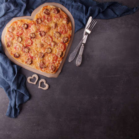 Romantic dinner in rustic style. Heart shaped pizza, blue napkin and cutlery on dark table