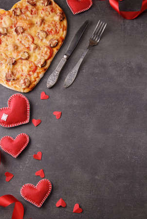 Romantic dinner, pizza heart, bright red hearts and cutlery. Vertical image. Top view Standard-Bild