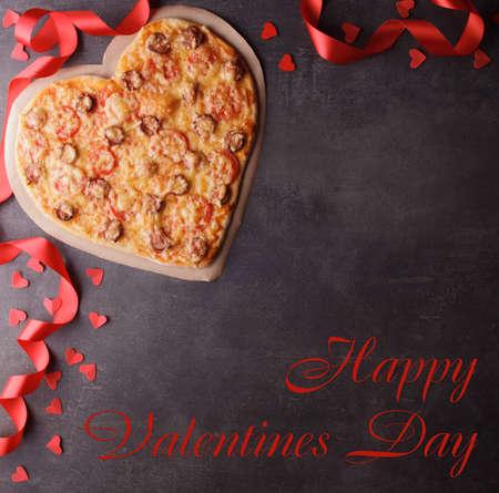 Happy valentine's day lettering, pizza heart, red ribbon on dark background. Top view Standard-Bild