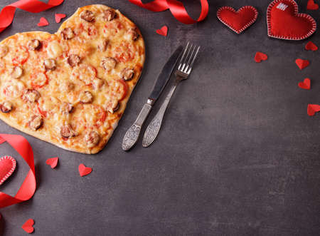 Romantic image. Pizza in the form of a heart, decor from a red ribbon and a heart. Blank space for inscription. Top view