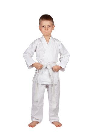 The sport is karate. Serious boy in white kimono isolated on white background Archivio Fotografico