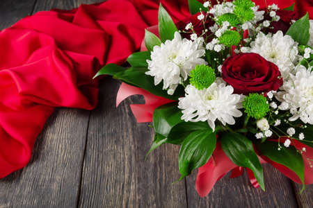 Bouquet of scarlet roses and chrysanthemums on a wooden background and fabric Archivio Fotografico