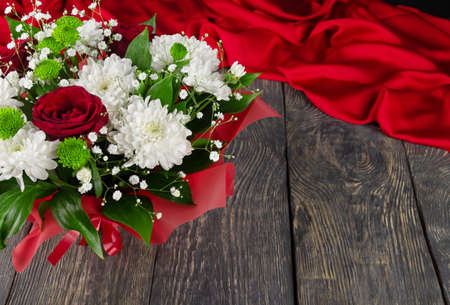 Bright bouquet of roses and white chrysanthemums on a wooden background and scarlet fabric Archivio Fotografico