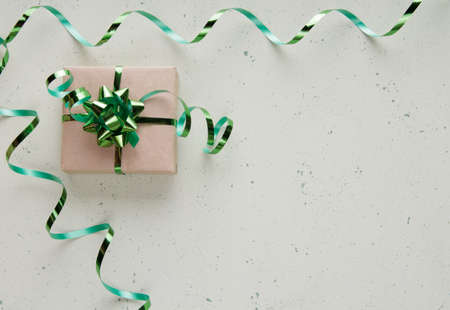Top view. Gift box with green ribbon and bow on light background