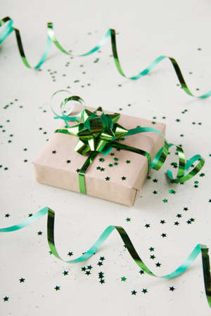 Gift box with a beautiful green bow on a light background with confetti in the form of stars