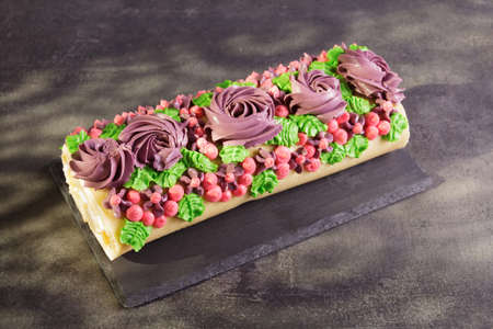 Appetizing roll with bright cream flowers on a dark background