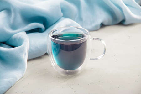 Blue tea in a transparent cup with a double bottom on a light background and a napkin Foto de archivo