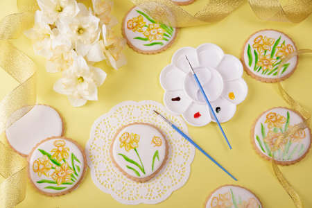 Spring holiday composition. The process of painting a gingerbread cookie decorated with daffodils