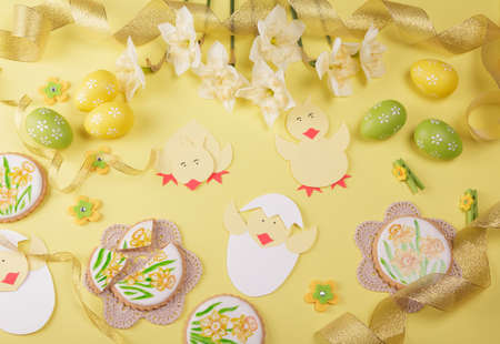 Happy easter. Hand painted gingerbread, easter eggs, spring flowers on yellow background Foto de archivo
