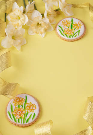 Festive spring composition. Handmade gingerbread cookies, daffodils and gold ribbon