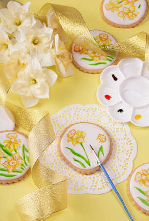 Spring mood. Top view. The pastry chef paints the gingerbread with a brush. Daffodil bouquet