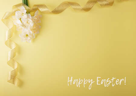 Happy easter. Top view. Festive background with place for an inscription, bright daffodils and gold ribbon