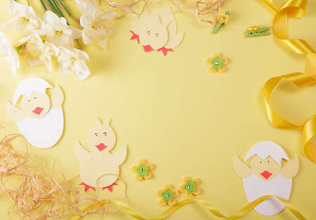 Festive composition for Easter. Chickens made of paper, golden ribbon and easter decor on yellow background Foto de archivo