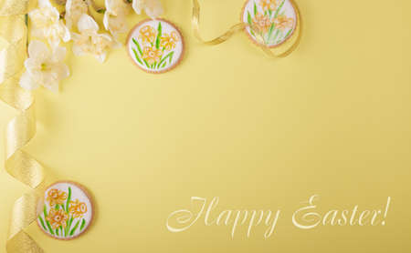 Festive spring card with the inscription Happy Easter. Flowers and handmade gingerbread cookies on a yellow background