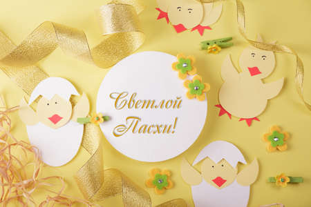 Inscription of light Easter in Russian. Easter card with chickens and golden ribbon on yellow background