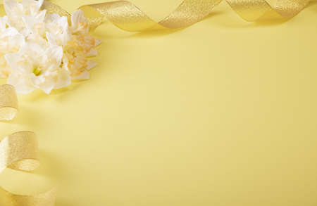 Fresh light daffodils and gold ribbon on a yellow background. Place for inscription Foto de archivo