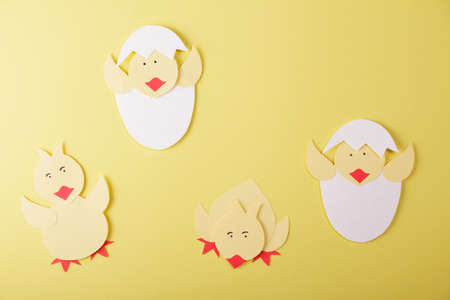 Top view. Origami. Chickens made of colored paper on a yellow background