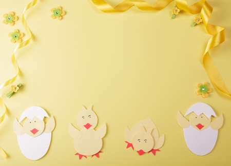 Bright composition of handmade chickens, golden ribbon and empty space for an inscription on a yellow background