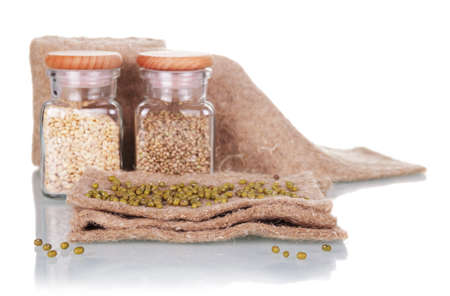 Set for growing microgreens. Linen mat, jars with seeds isolated on white background Foto de archivo