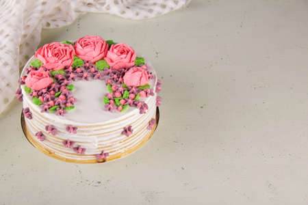 Delicious honey birthday cake with beautiful cream flowers on a light background with a place for congratulations