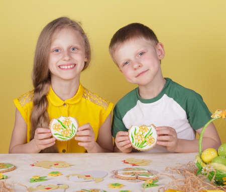 Happy kids with hand painted gingerbread on yellow background