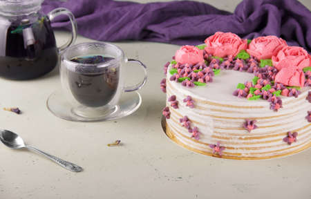 Blue tea and handmade honey cake on a light background with a napkin