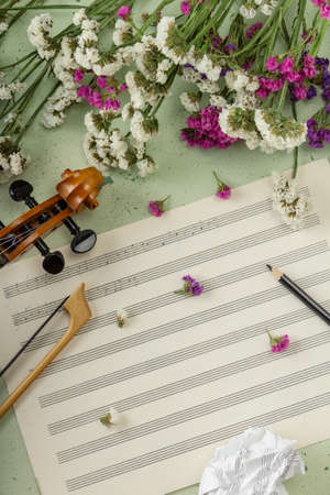 Unfinished piece of music. Music notes, crumpled sheet of music, violin curl and stem flowers