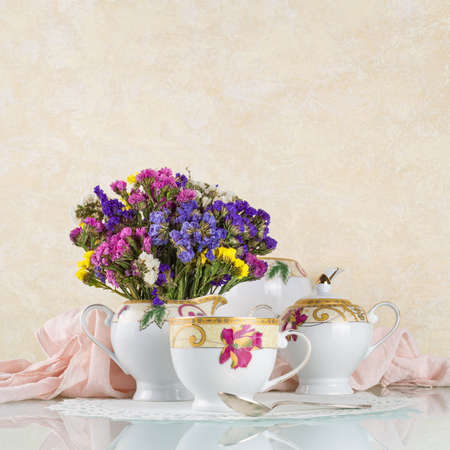 Good morning concept. Tea in beautiful cups and a teapot on a light background with dried flowers