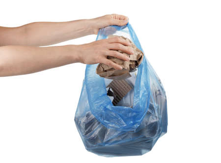 Female hands fold household waste paper and cardboard into trash bag isolated on white background