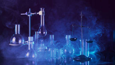 Chemical laboratory. Various test tubes and flasks, laboratory equipment in smoke with blue backlight