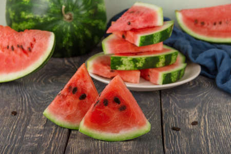 Sliced juicy tasty pieces of watermelon and whole fresh watermelon on dark boards
