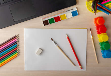 Online learning to draw using a laptop. Top view drawing paper, pencils and other supplies