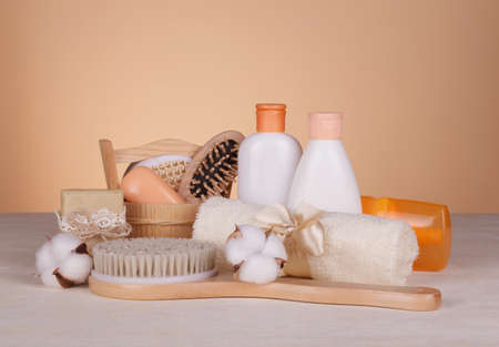 SPA set for home use. Body brush, scented soaps and skin care products on beige background