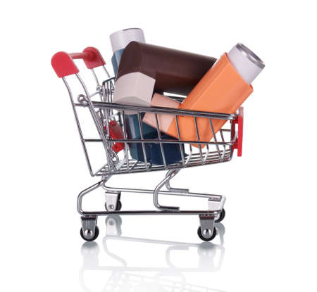 Supermarket trolley filled with breathing inhalers for lung disease isolated on white background