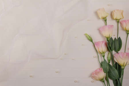 Delicate eustoma flowers on a light background decorated with a wedding veil