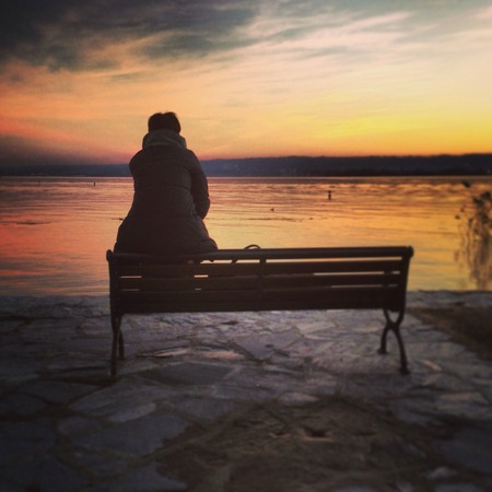 sitted: Woman in front of the sunset - Angera - Maggiore lake Stock Photo