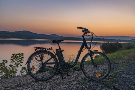 Electric bicycle with lights in summer evening Stok Fotoğraf
