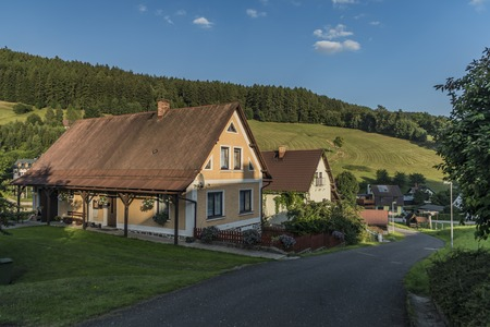 Sunny summer day in Krkonose mountains national park with countryside house
