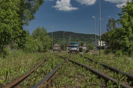 Blue motor train in Stare Mesto pod Sneznikem station in spring sunny day