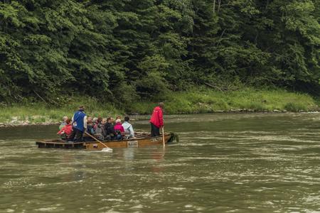 추운 여름 날에 Dunajec 강에서 승객과 목조 보트