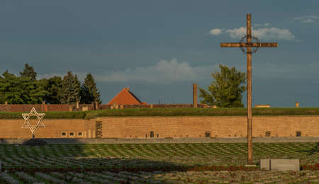 Cross in Terezin town in summer hot evening with big fortress