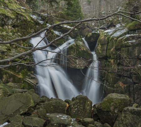 Waterfall of Cerny creek in Jizerske mountains in winter dark day
