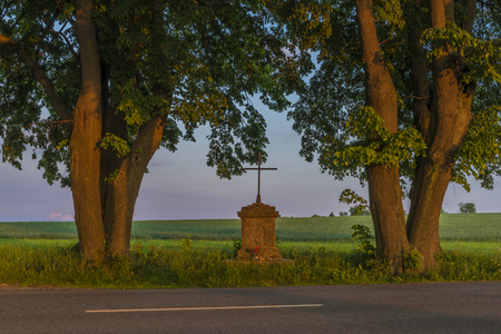 Cross with color sunset near Roprachtice village in spring nice sunny evening Stock Photo