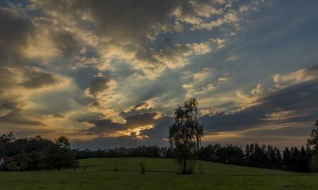 Cloudy orange blue sunset near Ceske Budejovice city in autumn evening
