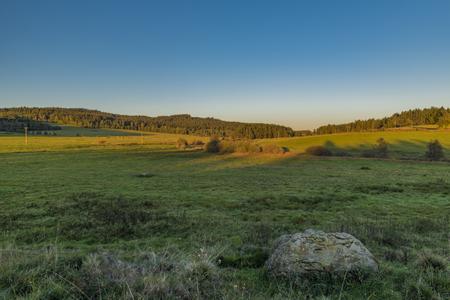 Sunset meadows with stones near Zbytiny village in national park Sumava