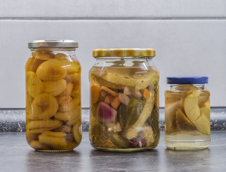 Pickles and stewed fruit in transparent glasses in the white kitchen