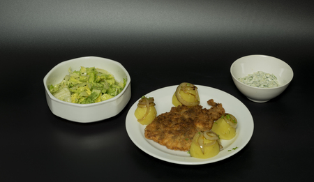 Fried wiener chicken fillet with potatoes and fried onion and two salads tzatziki and hungary salad Stock Photo