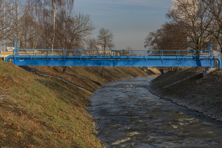 Blue pipes over Bilina river in Bilina town in winter sunny morning